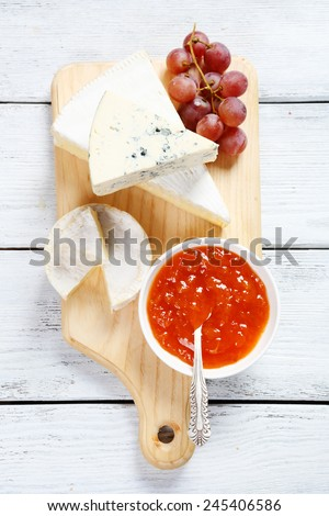 Cheese on a cutting board with jam, food - stock photo