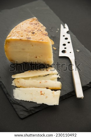 cheese on black slate platter  and knife - stock photo