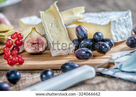 Cheese on the table. Sliced brie cheese on a wooden table and slices of figs - stock photo