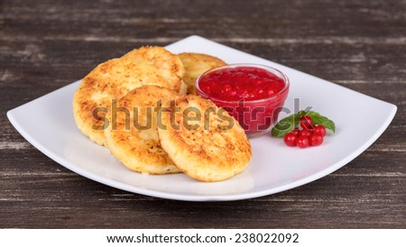 Cheese pancakes with honey and berry jam in white plate - stock photo