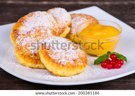 Cheese pancakes with honey in white plate - stock photo