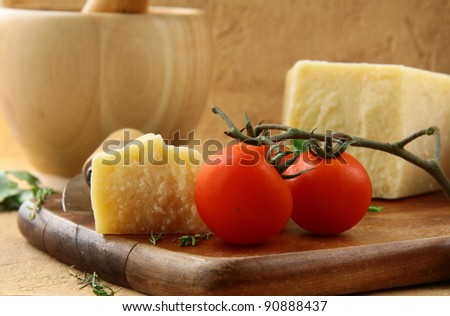 Cheese parmesan on a wooden board with tomatoes