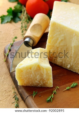 Cheese parmesan on a wooden board with tomatoes - stock photo
