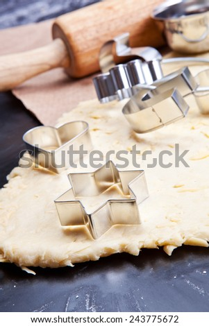 Cheese pastry dough with rolling pin on dark background - stock photo
