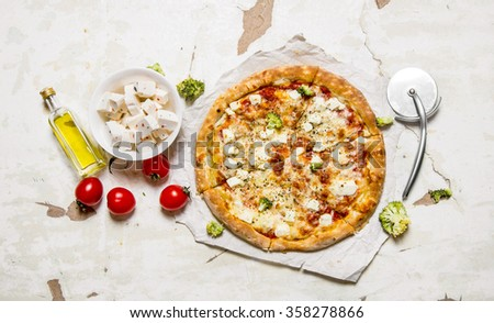 Cheese pizza with tomatoes and fresh cheese. On rustic background. Top view - stock photo