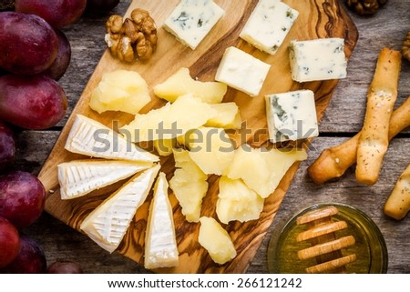 Cheese plate: Camembert cheese, blue cheese closeup, bread sticks, walnuts, honey, grapes on wooden table - stock photo