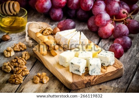 Cheese plate:  Camembert, Parmesan, blue cheese, bread sticks, walnuts, hazelnuts, honey, grapes  on wooden table - stock photo