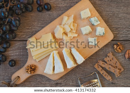 Cheese plate: Em mental, Camembert cheese, Parmesan, Blue cheese, crackers, walnuts, grapes on wooden table. Top view - stock photo