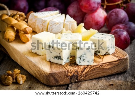 Cheese plate: Emmental, Camembert, Parmesan, blue cheese closeup, with bread sticks and grapes on wooden table - stock photo