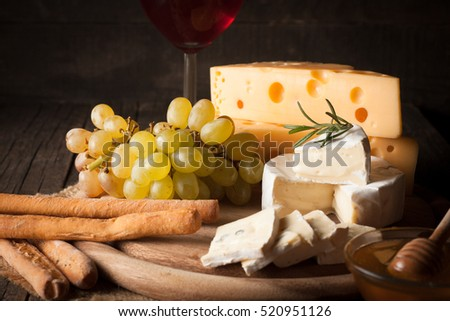 Cheese plate with brie, camambert, gauda with grapes,honey, crackers and nuts on a wooden background