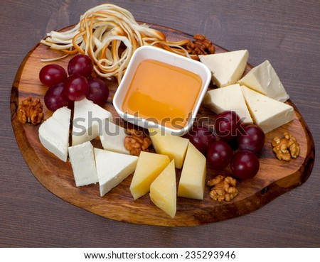 Cheese plate with cheeses Dorblu, Parmesan, Brie, Camembert and Roquefort in serving on the table from an old tree close-up