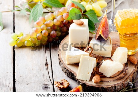 Cheese plate with honey, nuts and grape on a wooden background - stock photo
