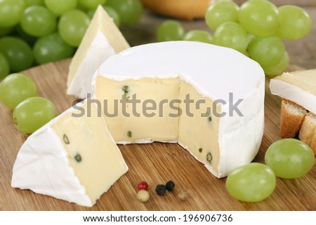 Cheese plate with soft cheese like Camembert or Brie on a wooden board