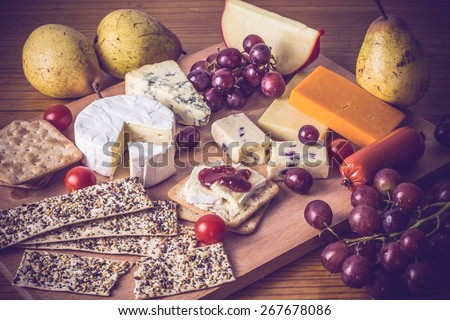 Cheese platter with crackers and grapes on wooden board. Rustic cheese selection with fruit and vegetables with a vintage,  blue instagram filter applied. Festive food concept - stock photo