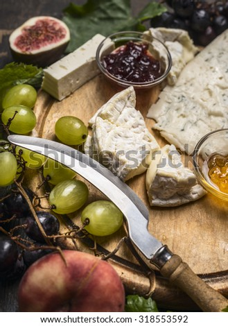 cheese platter with Gorgonzola ,,Camembert and honey and jam, light and dark grapes peaches, knife for cheese on wooden cutting board close up - stock photo