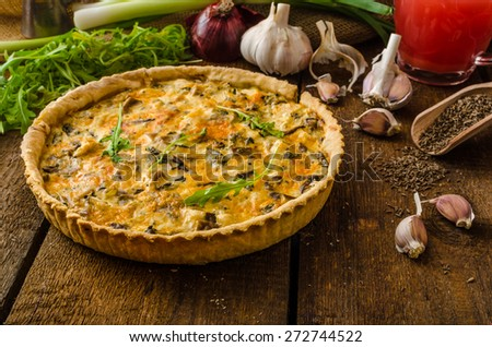Cheese Quiche with chicken, arugula and mushrooms, homemade, wood desk - stock photo