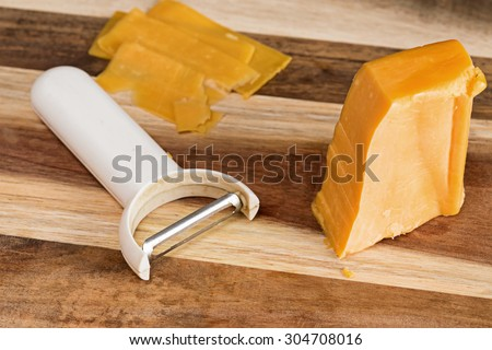 Cheese slicer with cheddar cheese block on a wooden background. - stock photo