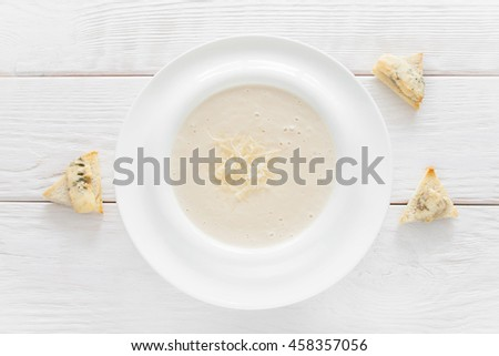 Cheese soup-puree with canape on white wooden background, flat lay. Homemade organic cream-soup with bruschetta slices - stock photo