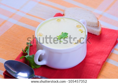 Cheese soup serves on a yellow tablecloth
