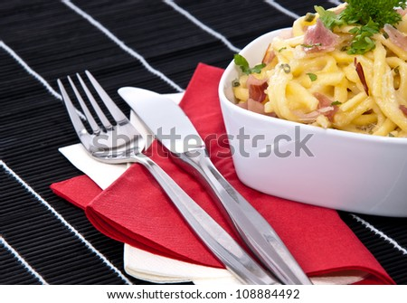 Cheese Spaetzle decorated with herbs and cutlery (on black background)
