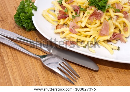 Cheese Spaetzle decorated with parsley on a plate (bamboo background) - stock photo