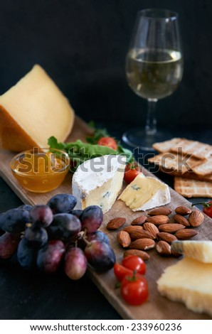 Cheese tasting platter with hard, soft, white rind assorted cheese, jam, grapes, raw almonds, cherry tomatoes, crackers and wine, perfect party entertaining gourmet food - stock photo