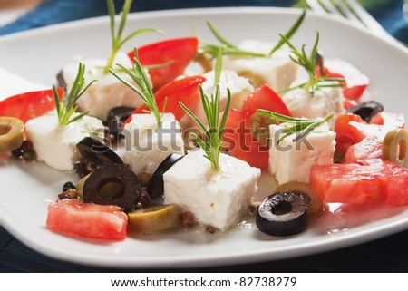 Cheese, tomato and olives salad with rosemary and olive oil