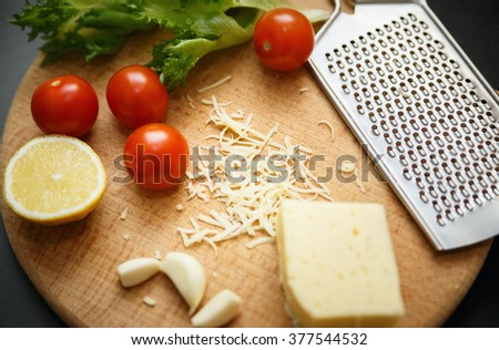Cheese, tomatoes, garlic with grater on wooden catting board