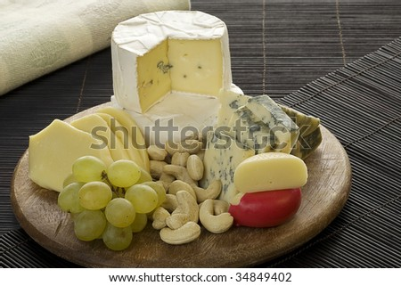 Cheese variety and nuts on a wood platter - stock photo