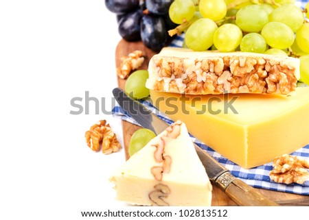 Cheese variety with white and black grapes on a cutting board. Isolated on white with copy space.