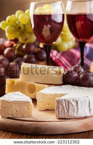 Cheese with a bottle and glasses of red wine on wooden table