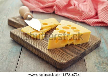 Cheese with big holes and knife on wooden cutting board - stock photo