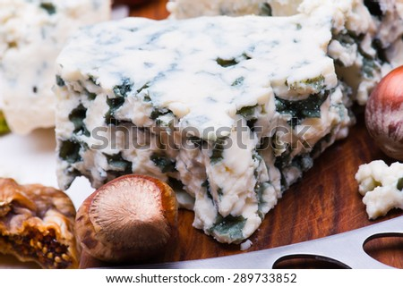 Cheese with dried fruits and nuts on wooden board  - stock photo