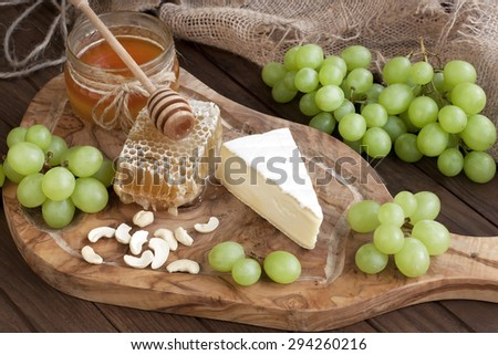 Cheese with grapes, honey and nuts on dark wooden background