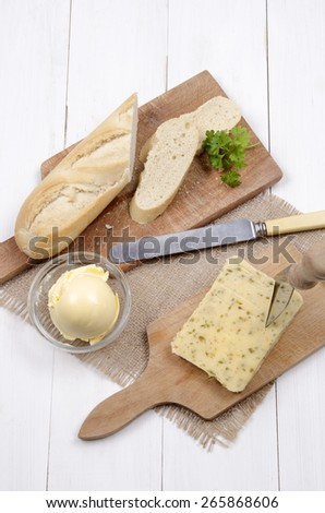 cheese with jalapeno chili and baguette, margarine and parsley with cheese knife on wooden board - stock photo