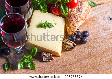 cheese with red wine and walnuts. food and beverages. selective focus. low key picture