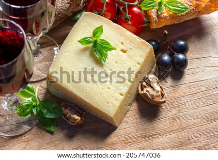 cheese with red wine, walnuts and grapes. food background. low key style picture