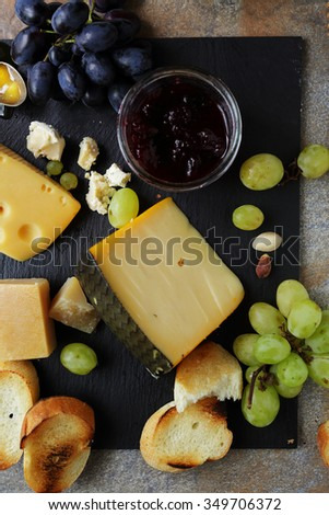 cheese with ripe grapes, food top view