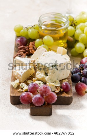 cheeseboard, fresh grapes and honey on a white background, vertical, closeup