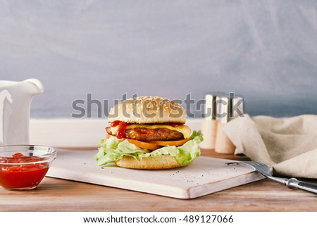 cheeseburger on a white chopping board