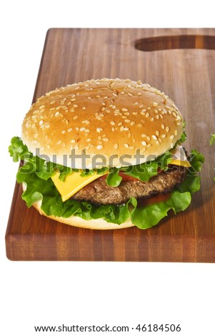Cheeseburger on wooden cutting board isolated on white.