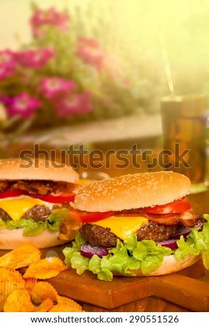 Cheeseburger on wooden table in a park - stock photo