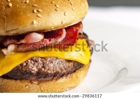 Cheeseburger with bacon on white plate - stock photo