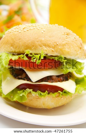 Cheeseburger with beer on background