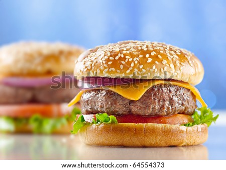 cheeseburger with blue background and selective focus - stock photo
