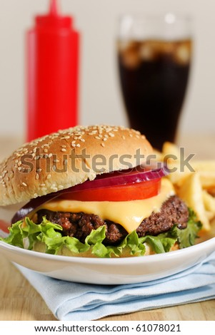 cheeseburger with french fries on a white plate with cola drink and ketchup in the background. Shallow depth of field. - stock photo