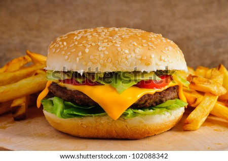 Cheeseburger with french fries on a wooden plate - stock photo