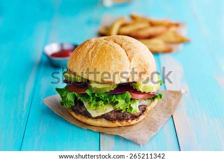cheeseburger with fries and ketchup on rustic table top - stock photo