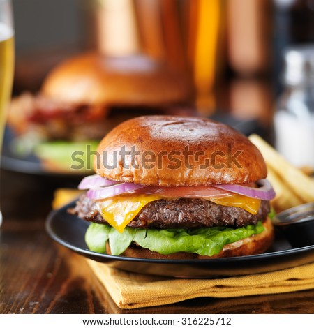 cheeseburgers and fries on table top with onion, tomato, lettuce and cheese - stock photo