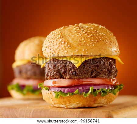 cheeseburgers on wooden board with lettuce, tomato and onion - stock photo